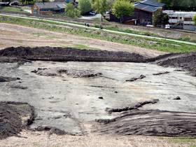 Det ferdig utgravde gudehovet i form av den runde steinsettingen med en åpning midt i det ryddede området. Jordvollen bak viser hvor tykt jordlag som i sin tid ble lagt over gudehovet for å skjule det.