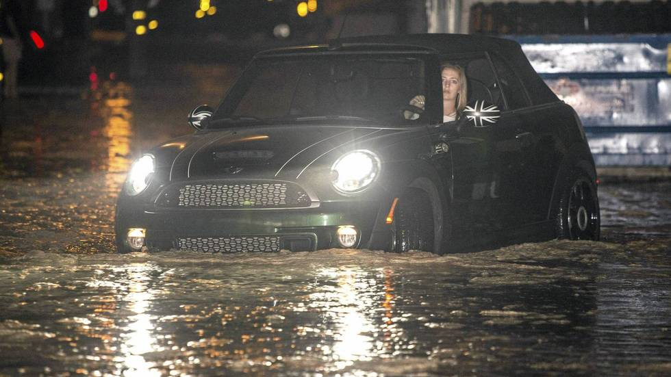 En kvinne prøver å redde bilden ut av en oversvømmet gate i Seal Beach, California.